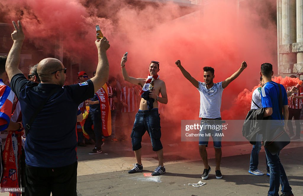 Atletico Madrid fans let off red smoke bombs and flares outside the central station ahead of the UEFA Champions League Final match between Real Madrid and Club Atletico de Madrid at Stadio Giuseppe Meazza on May 28, 2016 in Milan, Italy. (Photo by Catherine Ivill - AMA/Getty Images