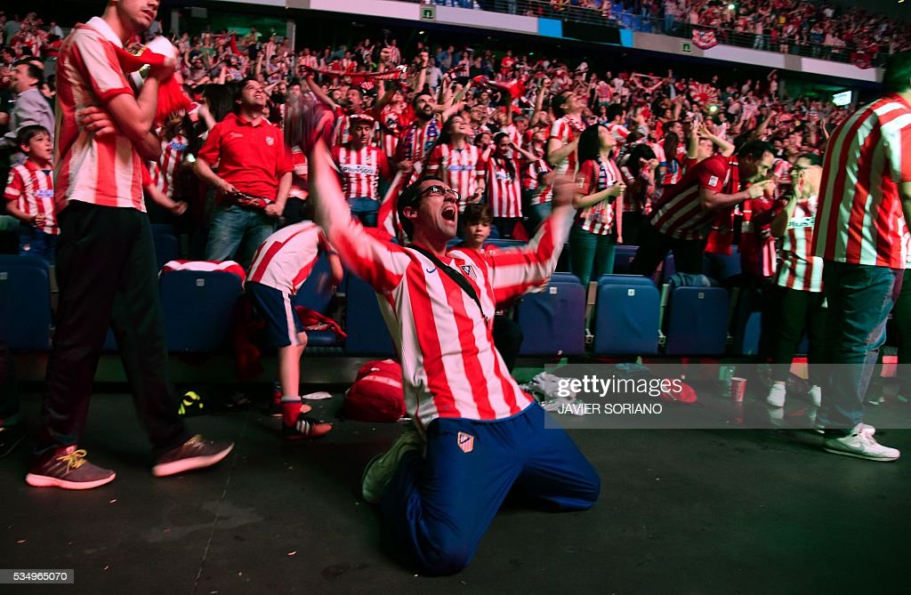 Atletico Madrid football club supporters celebrate their team's goal as they watch on a big screen at the Palacio de Deportes de la Communidad de Madrid, (Barclaycard Center), in Madrid on May 28, 2016 the UEFA Champions League final foobtall match between Real Madrid CF, Club Atletico de Madrid held in Milan, Italy. / AFP / JAVIER