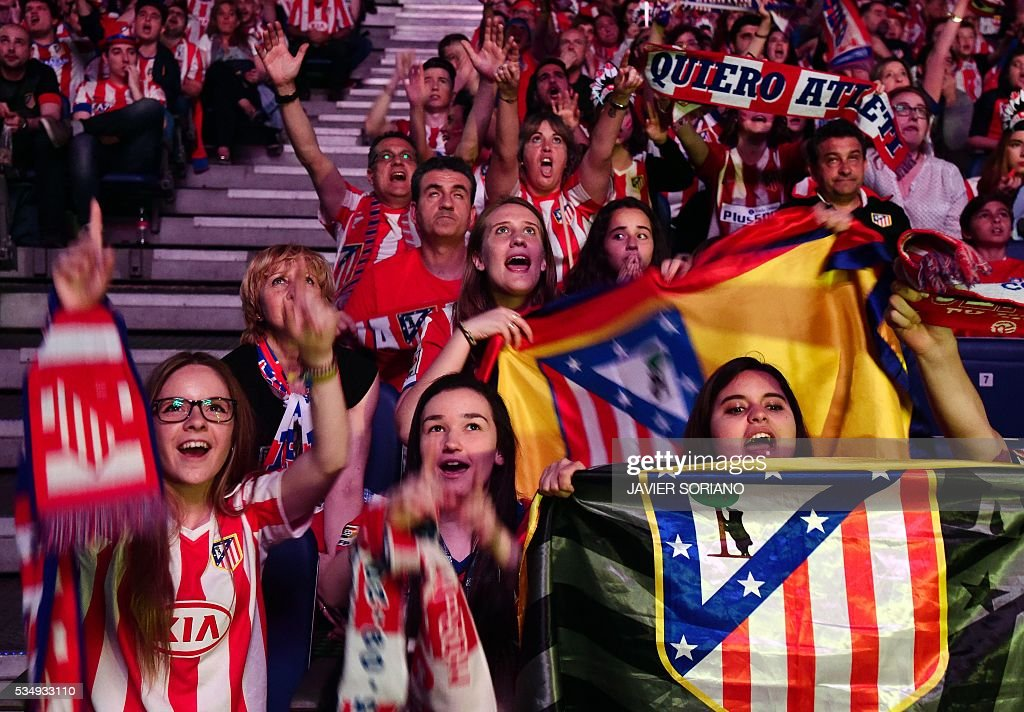 Atletico Madrid football club supporters cheers their team as they watch on a big screen at the Palacio de Deportes de la Communidad de Madrid, (Barclaycard Center), in Madrid on May 28, 2016 the UEFA Champions League final foobtall match between Real Madrid CF, Club Atletico de Madrid held in Milan, Italy. / AFP / JAVIER