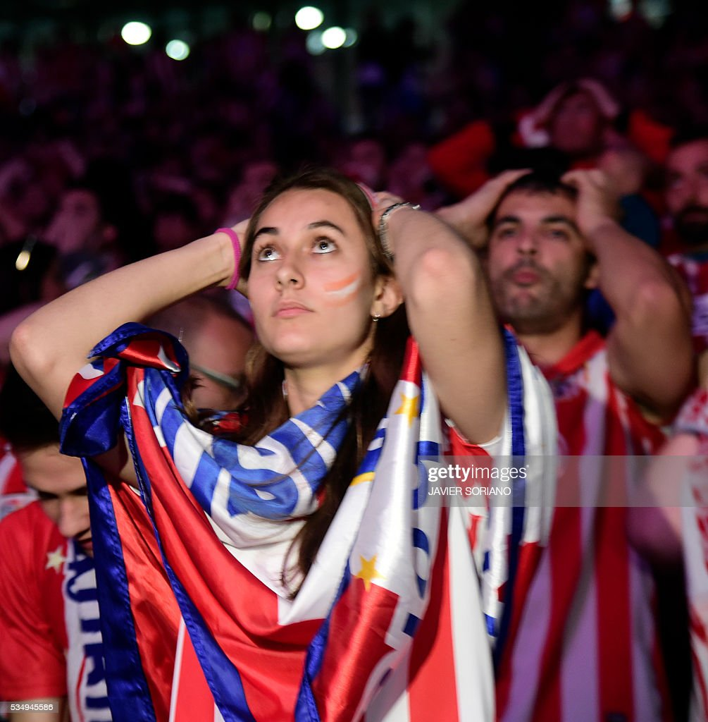 Atletico Madrid football club supporters gesture as they watch on a big screen at the Palacio de Deportes de la Communidad de Madrid, (Barclaycard Center), in Madrid on May 28, 2016 the UEFA Champions League final foobtall match between Real Madrid CF, Club Atletico de Madrid held in Milan, Italy. / AFP / JAVIER