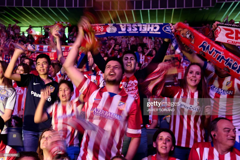 Atletico Madrid football club supporters wave scarves before watching on a big screen at the Palacio de Deportes de la Communidad de Madrid, (Barclaycard Center), in Madrid on May 28, 2016 the UEFA Champions League final foobtall match between Real Madrid CF, Club Atletico de Madrid held in Milan, Italy. / AFP / JAVIER