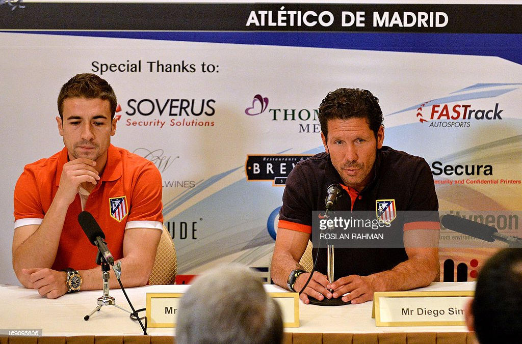 Atletico Madrid head coach Diego Simone (R) and team captain Gabriel Fernandez (L) attend a pre-match press conference in Singapore on May 20, 2013. Atletico Madrid, the newly-crowned kings of Spain, are in town for a friendly football match against a Singapore selection team on May 22.