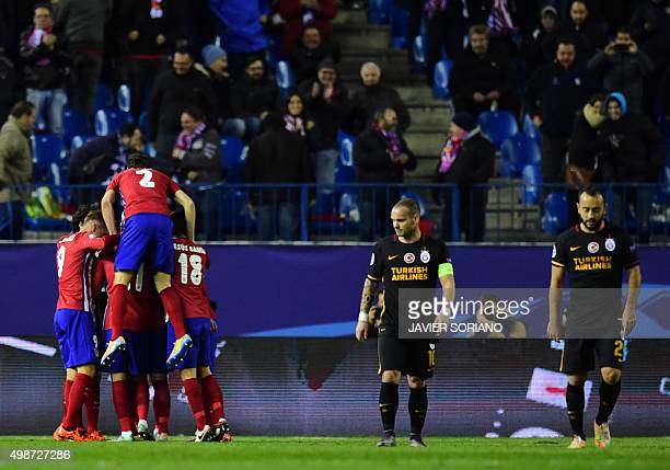 Atletico Madrid players celebrate after scoring their second goal as Galatasaray's Dutch midfielder Wesley Sneijder and Galatasaray's midfielder...