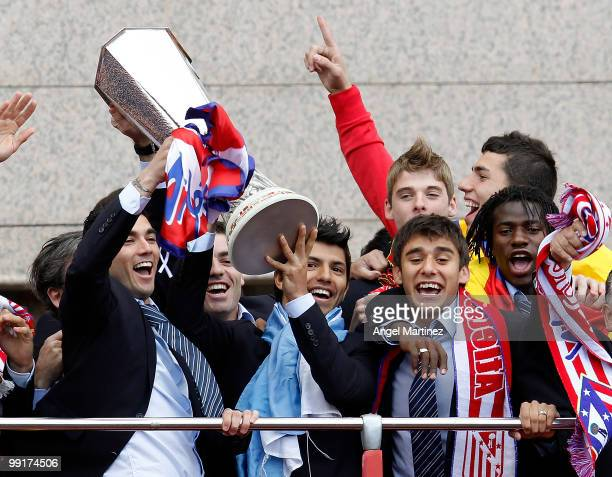 Atletico Madrid players Jose Antonio Reyes Sergio Aguero Salvio and Ibrahima celebrate with the trophy on the top of an open bus in Madrid the day...