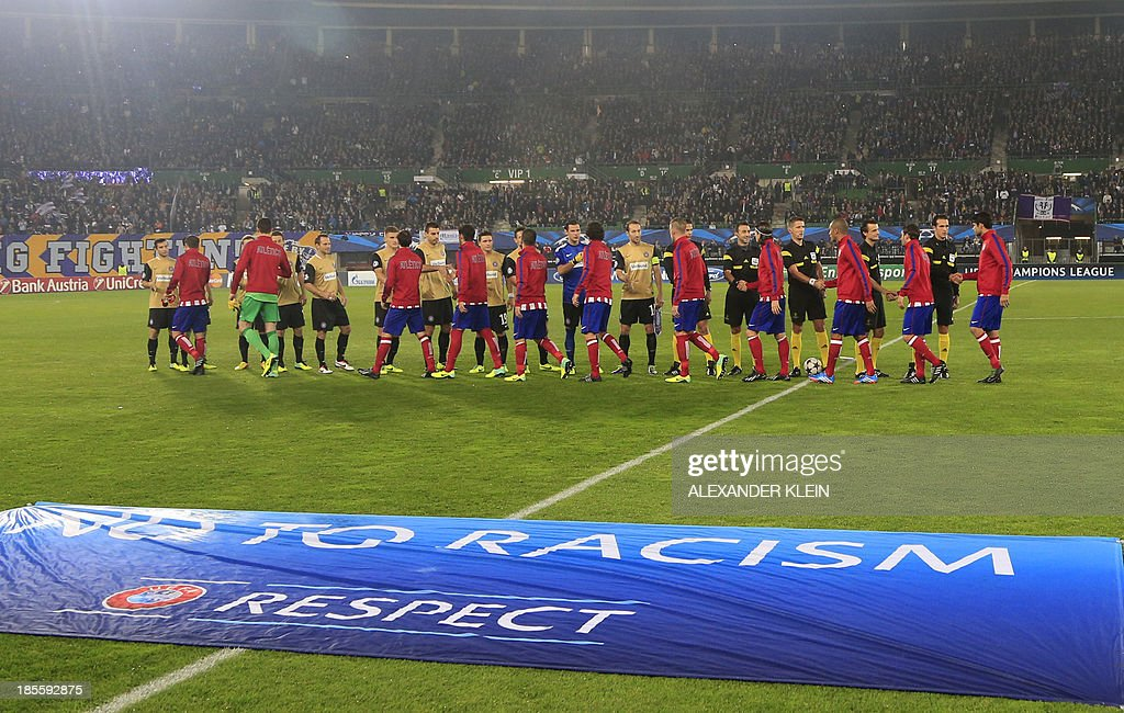 Atletico Madrid's and Austria Wien's team players shake hands next to the UEFA 'No to Racism' banner, ahead of the start of a group stage UEFA Champions League football match between Austria Wien and Atletico de Madrid on October 22, 2013 at the Ernst Happel stadium in Vienna. Atletico Madrid won 3-0. AFP PHOTO / ALEXANDER KLEIN
