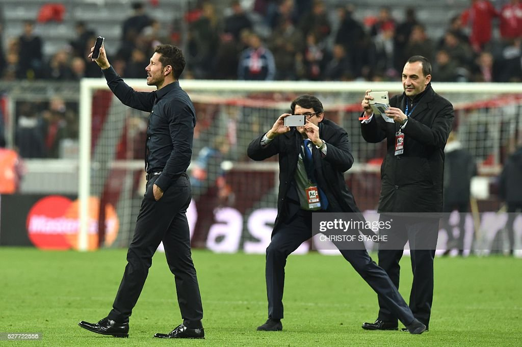 Atletico Madrid's Argentinian coach Diego Simeone (L) and staff members celebrate with their smartphones qualifying for the final after the UEFA Champions League semi-final, second-leg football match between FC Bayern Munich and Atletico Madrid in Munich, southern Germany, on May 3, 2016. / AFP / Christof Stache