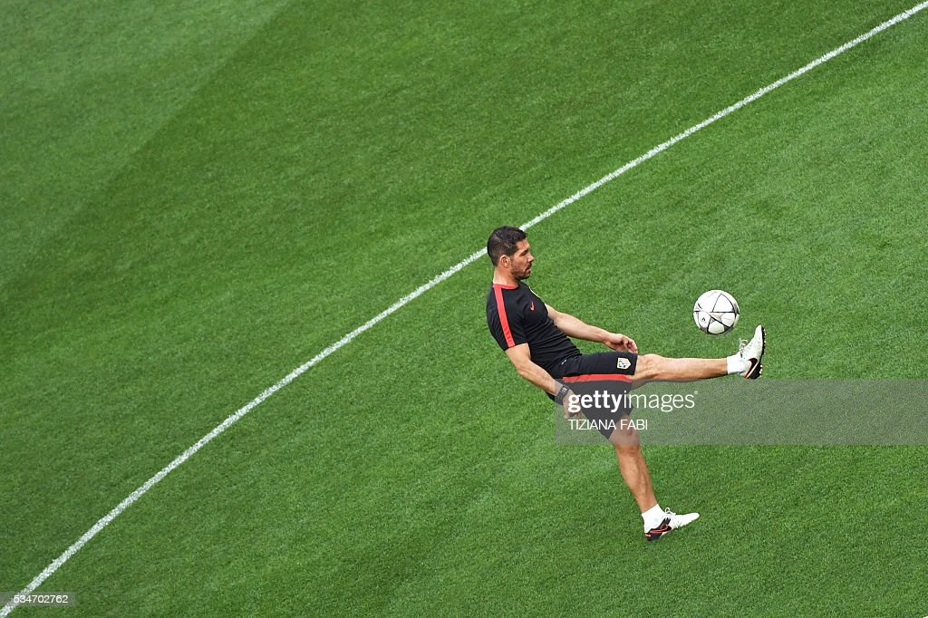 Atletico Madrid's Argentinian coach Diego Simeone controls the ball during a training session at the San Siro Stadium in Milan, on May 27, 2016, on the eve of the UEFA Champions League final foobtall match between Real Madrid and Atletico Madrid. / AFP / TIZIANA