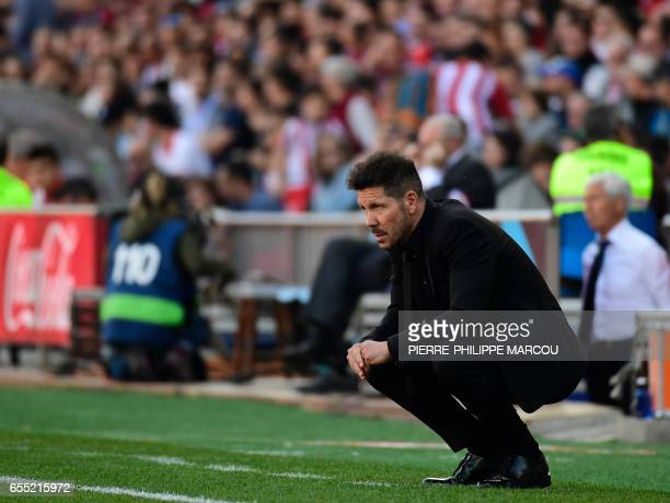 Atletico Madrid's Argentinian coach Diego Simeone crouches on the sideline during the Spanish league football match Club Atletico de Madrid vs...