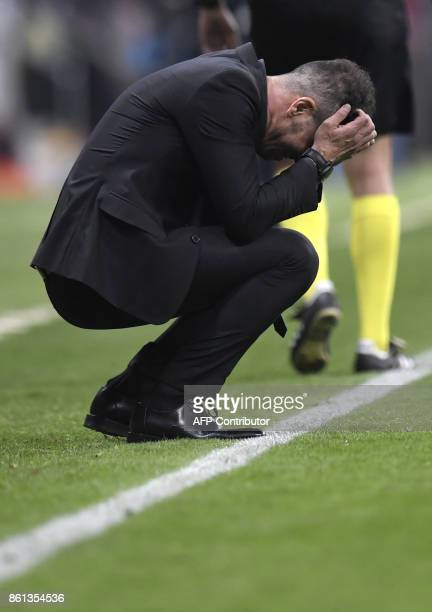 Atletico Madrid's Argentinian coach Diego Simeone crouches on the sideline during the Spanish league football match Club Atletico de Madrid vs FC...