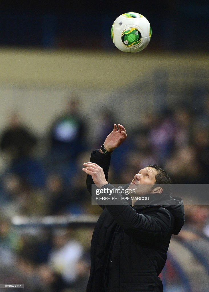 Atletico Madrid's Argentinian coach Diego Simeone eyes the ball during the Spanish Copa del Rey (King's Cup) quarter-final first leg football match Club Atletico de Madrid vs Real Betis at the Vicente Calderon stadium in Madrid on January 17, 2013.