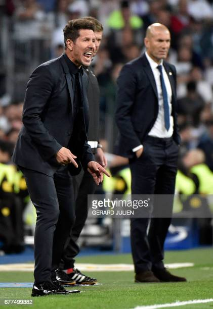 Atletico Madrid's Argentinian coach Diego Simeone gestures beside Real Madrid's French coach Zinedine Zidane during the UEFA Champions League...