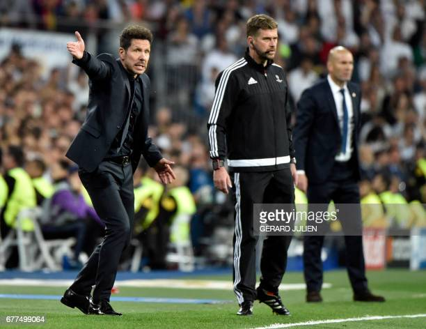 Atletico Madrid's Argentinian coach Diego Simeone gestures close to Real Madrid's French coach Zinedine Zidane during the UEFA Champions League...