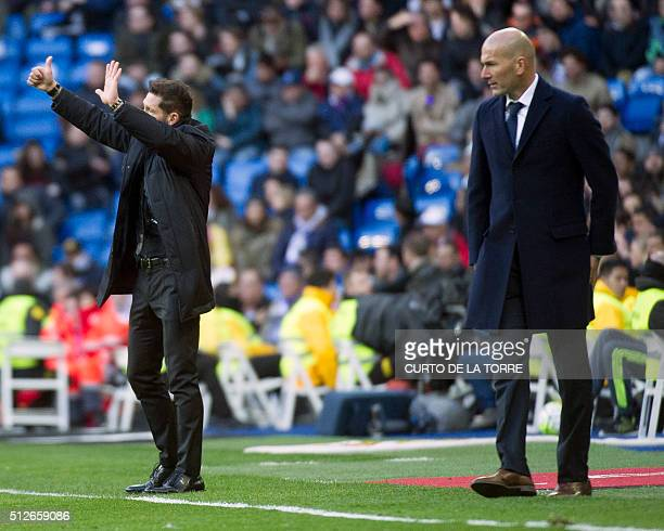 Atletico Madrid's Argentinian coach Diego Simeone gestures next to Real Madrid's French coach Zinedine Zidane during the Spanish league football...