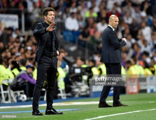 Atletico Madrid's Argentinian coach Diego Simeone gestures on the sideline with Real Madrid's French coach Zinedine Zidane in background during the...