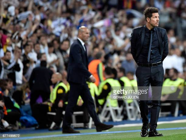 Atletico Madrid's Argentinian coach Diego Simeone looks on beside Real Madrid's French coach Zinedine Zidane during the UEFA Champions League...