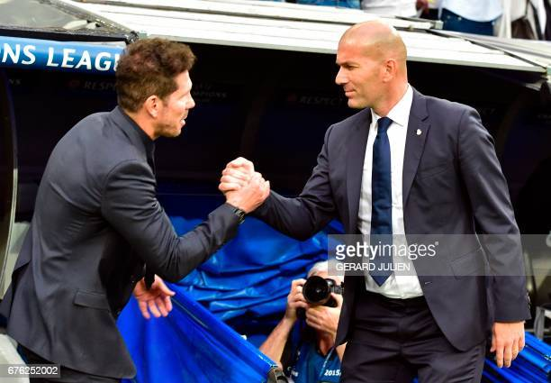 Atletico Madrid's Argentinian coach Diego Simeone shakes hands with Real Madrid's French coach Zinedine Zidane beofre the UEFA Champions League...