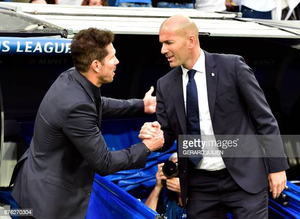 Atletico Madrid's Argentinian coach Diego Simeone shakes hands wwith Real Madrid's French coach Zinedine Zidane before the UEFA Champions League...