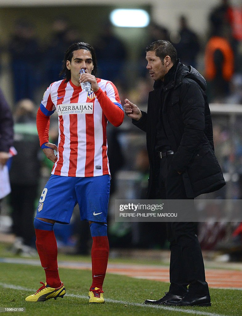 Atletico Madrid's Argentinian coach Diego Simeone (R) speaks with Atletico Madrid's Colombian forward Radamel Falcao during the Spanish Copa del Rey (King's Cup) quarter-final first leg football match Club Atletico de Madrid vs Real Betis at the Vicente Calderon stadium in Madrid on January 17, 2013.