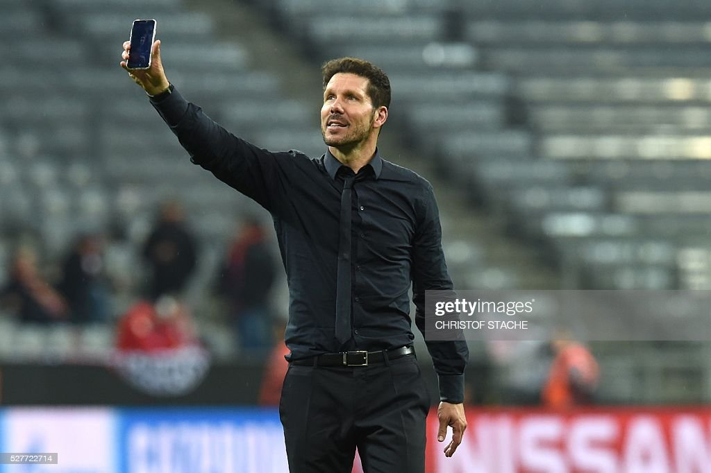 Atletico Madrid's Argentinian coach Diego Simeone uses his smartphone while celebrating qualifying for the final after the UEFA Champions League semi-final, second-leg football match between FC Bayern Munich and Atletico Madrid in Munich, southern Germany, on May 3, 2016. / AFP / Christof Stache