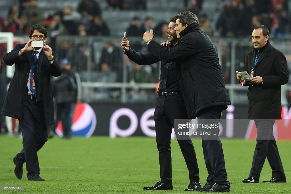 Atletico Madrid's Argentinian coach Diego Simeone (C) uses his smartphone while celebrating qualifying for the final after the UEFA Champions League semi-final, second-leg football match between FC Bayern Munich and Atletico Madrid in Munich, southern Germany, on May 3, 2016. / AFP / Christof Stache