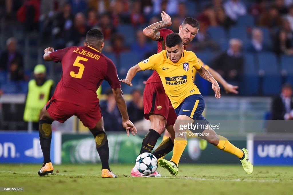 Atletico Madrid's Argentinian forward Angel Correa (C) makes his way through Roma's defender Juan Jesus (L) and Roma's Serbian defender Aleksandar Kolarov during the UEFA Champions League Group C football match between AS Roma and Atletico Madrid on September 12, 2017 at the Olympic stadium in Rome. / AFP PHOTO / Filippo MONTEFORTE