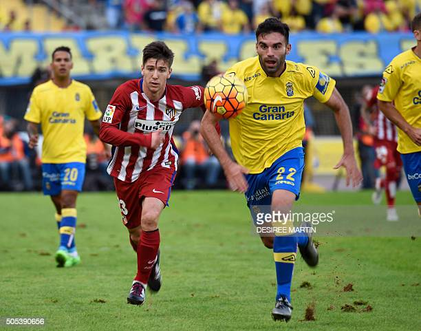 Atletico Madrid's Argentinian forward Luciano Vietto vies with Las Palmas' defender Javier Garrido during the Spanish league football match UD Las...