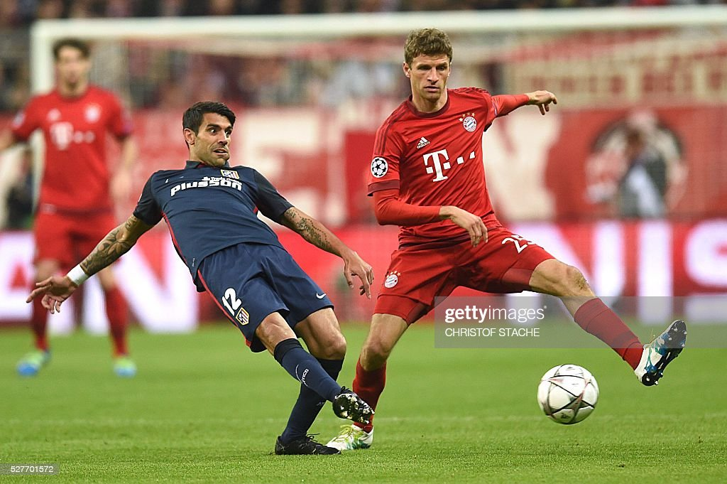 Atletico Madrid's Argentinian midfielder Augusto Fernandez (L) and Bayern Munich's midfielder Thomas Mueller fight for the ball during the UEFA Champions League semi-final, second-leg football match between FC Bayern Munich and Atletico Madrid in Munich, southern Germany, on May 3, 2016. / AFP / Christof Stache