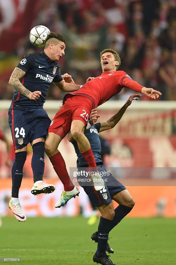 Atletico Madrid's Argentinian midfielder Augusto Fernandez (L), Bayern Munich's midfielder Thomas Mueller (C) and Atletico Madrid's Argentinian midfielder Augusto Fernandez fight for the ball during the UEFA Champions League semi-final, second-leg football match between FC Bayern Munich and Atletico Madrid in Munich, southern Germany, on May 3, 2016. / AFP / Christof Stache