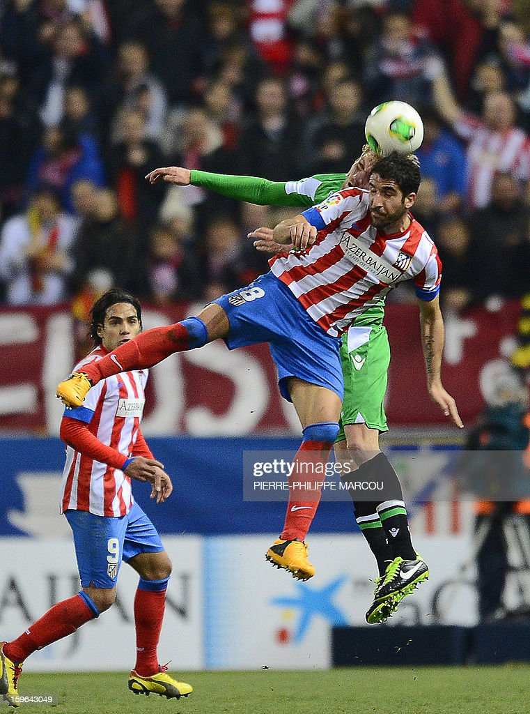 Atletico Madrid's Argentinian midfielder Raul García (R) vies with Betis' Polish defender Damien Perquis during the Spanish Copa del Rey (King's Cup) quarter-final first leg football match Club Atletico de Madrid vs Real Betis at the Vicente Calderon stadium in Madrid on January 17, 2013. AFP PHOTO/ PIERRE-PHILIPPE MARCOU