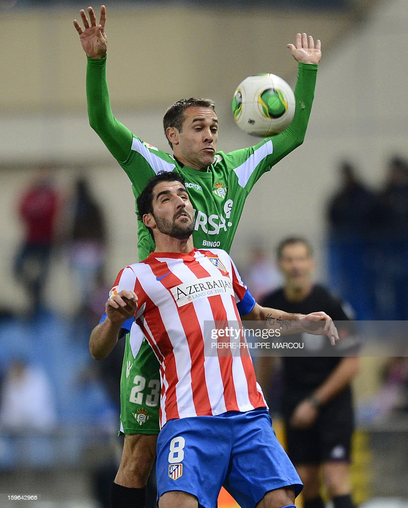 Atletico Madrid's Argentinian midfielder Raul Garcia (Bottom) vies with Betis' defender Nacho during the Spanish Copa del Rey (King's Cup) quarter-final first leg football match Club Atletico de Madrid vs Real Betis at the Vicente Calderon stadium in Madrid on January 17, 2013.