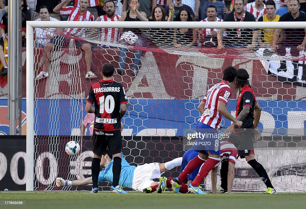 Atletico Madrid's Argentinian midfielder Raul Garcia (2ndR) watches the ball after scoring on a header during the Spanish league football match Atletico Madrid vs Rayo Vallecano at Vicente Calderon stadium in Madrid on August 25, 2013.