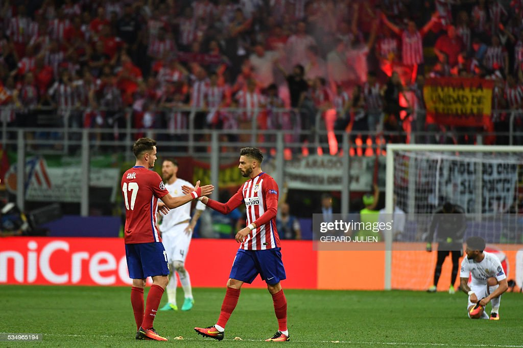 Atletico Madrid's Belgian forward Yannick Ferreira Carrasco (R) celebrates with teammate Atletico Madrid's Spanish midfielder Saul Niguez after he scored during the UEFA Champions League final football match between Real Madrid and Atletico Madrid at San Siro Stadium in Milan, on May 28, 2016. / AFP / GERARD