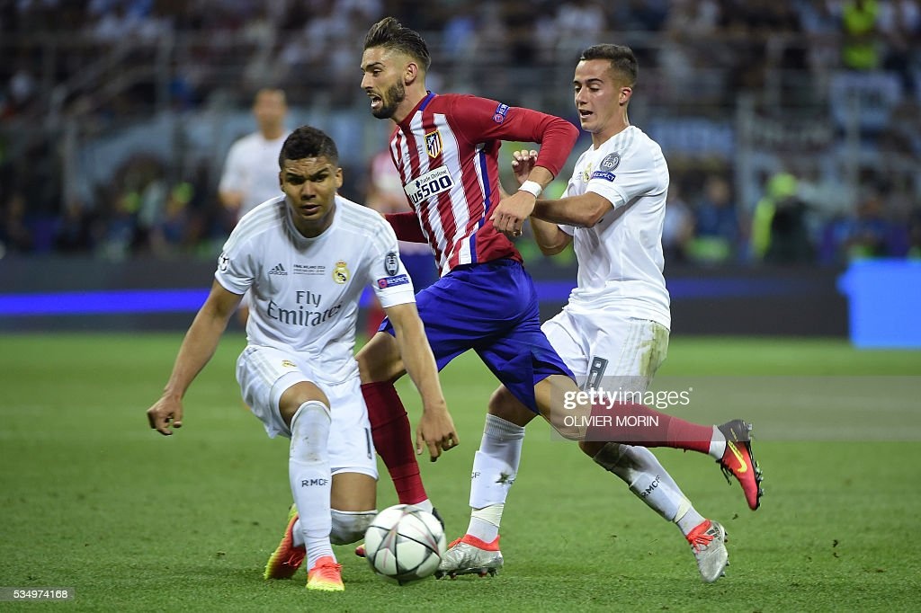 Atletico Madrid's Belgian forward Yannick Ferreira Carrasco (C) is challenged for the ball by Real Madrid's Brazilian midfielder Casemiro (L) and Real Madrid's Spanish midfielder Lucas Vazquez during the UEFA Champions League final football match between Real Madrid and Atletico Madrid at San Siro Stadium in Milan, on May 28, 2016. / AFP / OLIVIER