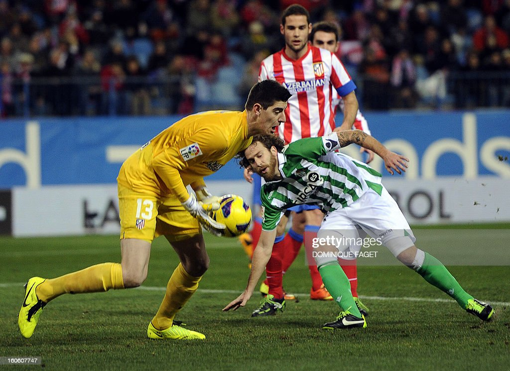 Atletico Madrid's Belgian goalkeeper Thibaut Courtois (L) vies with Betis' midfielder Jose Canas (R) during the Spanish league football match Atletico de Madrid vs Real Betis at the Vicente Calderon stadium in Madrid on February 3, 2013.
