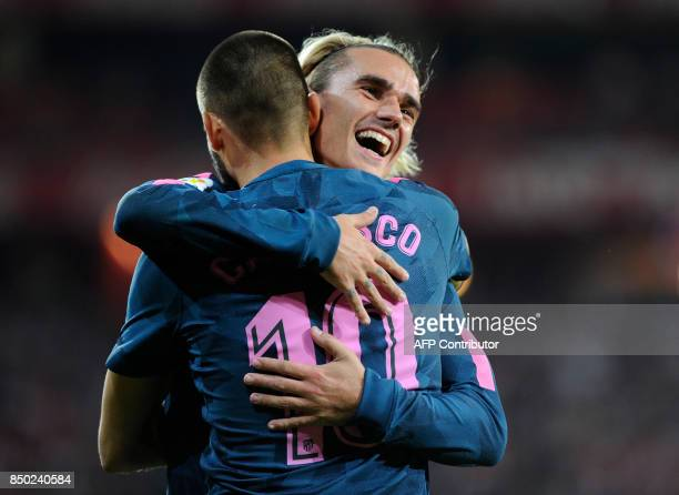 Atletico Madrid's Belgian midfielder Yannick Ferreira Carrasco is congratulated by teammate French forward Antoine Griezmann after scoring his team's...