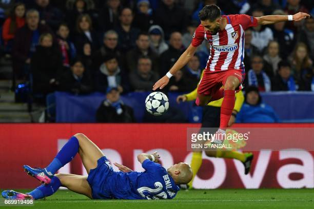 Atletico Madrid's Belgian midfielder Yannick Ferreira Carrasco jumps a tackle by Leicester City's French defender Yohan Benalouane during the UEFA...