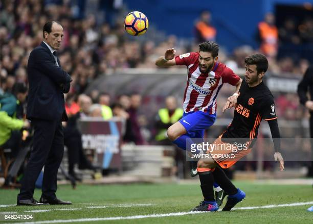 Atletico Madrid's Belgian midfielder Yannick Ferreira Carrasco vies with Valencia's defender Jose Gaya under the eyes of Valencia's coach Voro...
