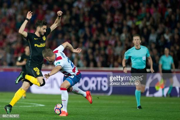 Atletico Madrid's Belgian midfielder Yannick Ferreira Carrasco vies with Granada's Icelandic defender Sverrir Ingi Ingason during the Spanish league...