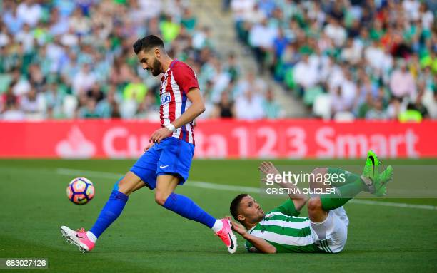 Atletico Madrid's Belgian midfielder Yannick Ferreira Carrasco vies for the ball with Betis' Danish defender Riza Durmisi during the Spanish league...