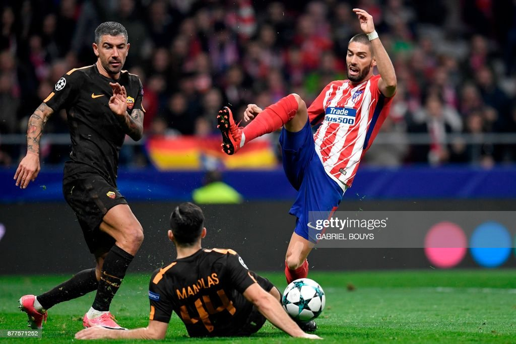 Atletico Madrid's Belgian midfielder Yannick Ferreira-Carrasco (R) challenges Roma's Croatian defender Aleksandar Kolarov (L) and Roma's Greek defender Kostas Manolas during the UEFA Champions League group C football match between Atletico Madrid and AS Roma at the Wanda Metropolitan Stadium in Madrid on November 22, 2017. /