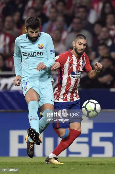 Atletico Madrid's Belgian midfielder Yannick FerreiraCarrasco vies with Barcelona's Spanish defender Gerard Pique during the Spanish league football...
