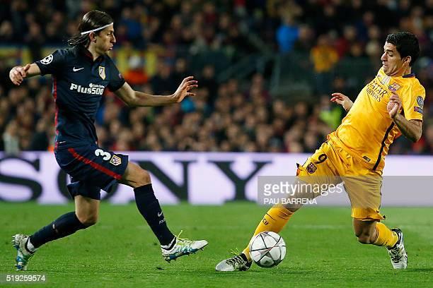 Atletico Madrid's Brazilian defender Filipe Luis vies with Barcelona's Uruguayan forward Luis Suarez during the UEFA Champions League quarter finals...