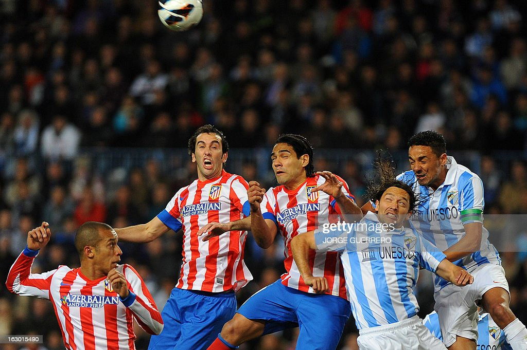 Atletico Madrid's Brazilian defender Joa Miranda de Souza, Uruguayan defender Diego Godin and Colombian forward Radamel Falcao vie with Malaga's Chilean midfielder Manuel Iturra and Brazilian defender Weligton during the Spanish league football match Malaga CF vs Atletico de Madrid on March 3, 2013 at Rosaleda stadium in Malaga.