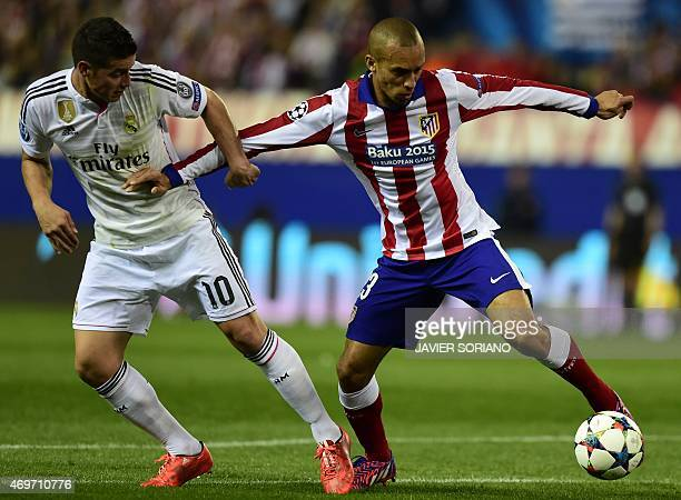 Atletico Madrid's Brazilian defender Joao Miranda vies with Real Madrid's Colombian midfielder James Rodriguez during the UEFA Champions League...