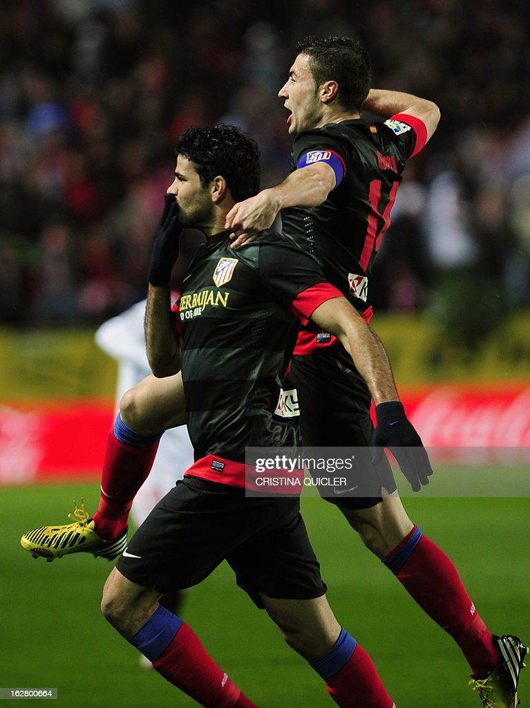 Atletico Madrid's Brazilian forward Diego da Silva Costa (L) celebrates after scoring during the Copa del Rey (King's Cup) semi-final second leg football match Sevilla FC vs Atletico de Madrid at the Ramon Sanchez Pizjuan staduim in Sevilla on February 27, 2013.