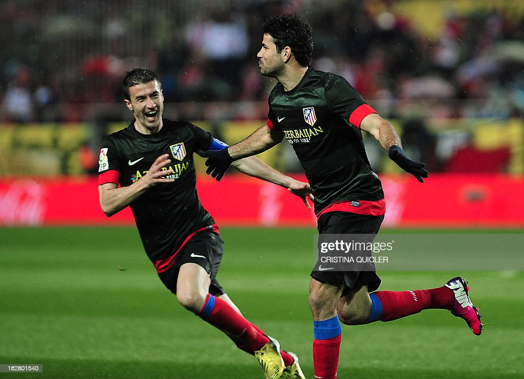 Atletico Madrid's Brazilian forward Diego da Silva Costa (R) celebrates after scoring during the Copa del Rey (King's Cup) semi-final second leg football match Sevilla FC vs Atletico de Madrid at the Ramon Sanchez Pizjuan staduim in Sevilla on February 27, 2013. AFP PHOTO / CRISTINA QUICLER
