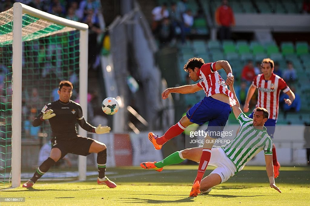 Atletico Madrid's Brazilian forward Diego da Silva Costa scores past Betis' defender Antonio Amaya during the Spanish league football match Real...