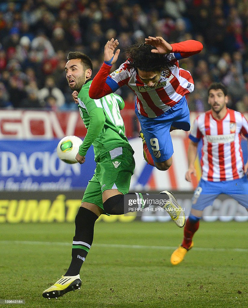 Atletico Madrid's Colombian forward Radamel Falcao (R) falls as he vies with Betis' defender Nacho during the Spanish Copa del Rey (King's Cup) quarter-final first leg football match Club Atletico de Madrid vs Real Betis at the Vicente Calderon stadium in Madrid on January 17, 2013.