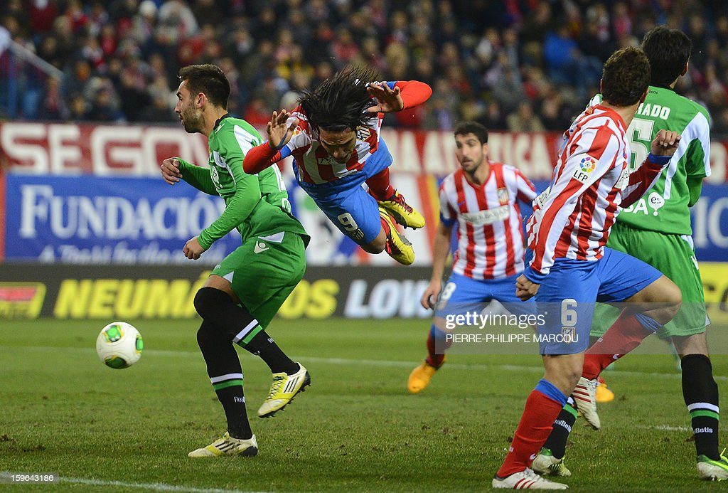 Atletico Madrid's Colombian forward Radamel Falcao (C) falls as he vies with Betis' defender Nacho (L) during the Spanish Copa del Rey (King's Cup) quarter-final first leg football match Club Atletico de Madrid vs Real Betis at the Vicente Calderon stadium in Madrid on January 17, 2013.