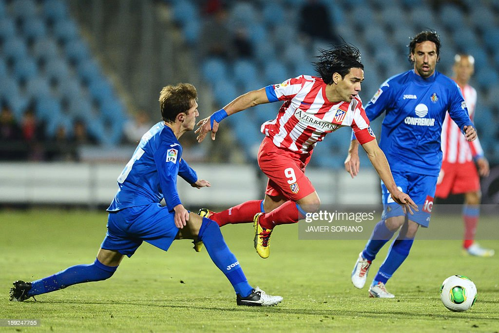 Atletico Madrid's Colombian forward Radamel Falcao (C) vies with Getafe's defender Rafael Lopez (L) and Getafe's midfielder Juan Antonio Rodriguez (R) during the Spanish Copa del Rey (King's Cup) round of 16, second leg, football match Getafe vs Atletico de Madrid at the Coliseum Alfonso Perez stadium on January 10, 2013.